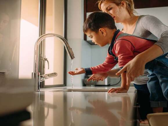 Little boy with mother washing hands in kitchen sink. Woman helping her son to wash hands in kitchen sink after cooking.